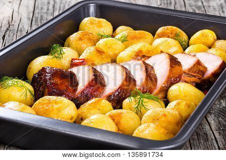 Oven Baked new potatoes with sea salt red bell pepper and pork tenderloin cutting into pieces in a baking dish on a wooden table close-up view from above