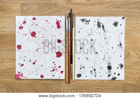 Two piece of papers spotted with ink and brushes in a wooden background