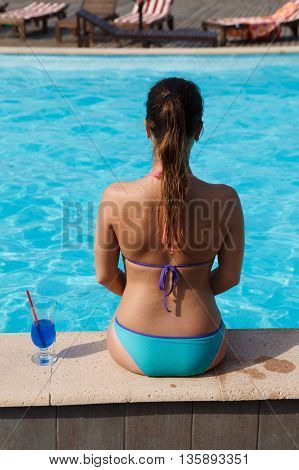 girl with blue cocktail near pool on the sun