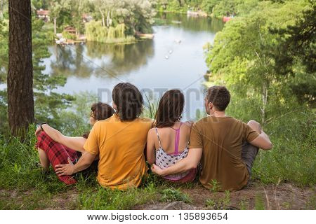 Rear view image of group of young friends sitting in a row by a lake and looking at a beautiful landscape view. Group of friends sitting by a lake and relaxing.