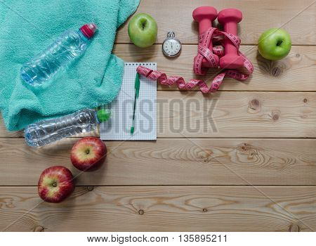 Healthy lifestyle concept. colored Apples notepad stopwatch dumbbells measure tape sport water bottle and turquoise towel on wooden table