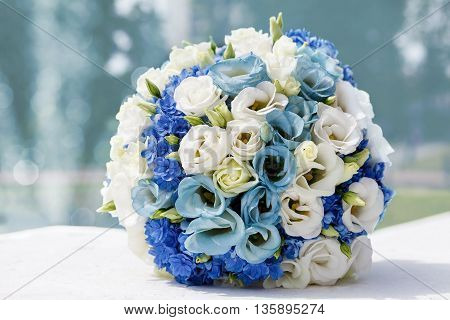 beautiful wedding bouquet of roses on the background of the fountain