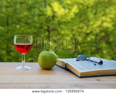 glass of wine green apple eyeglasses and book on table in the garden