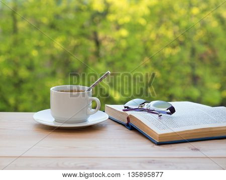 cup coffee glasses and book on summer trees background