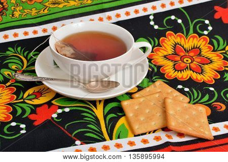 Cup with tea and biscuits on colorful tablecloth