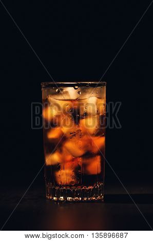 Glass of soda with ice on a black background