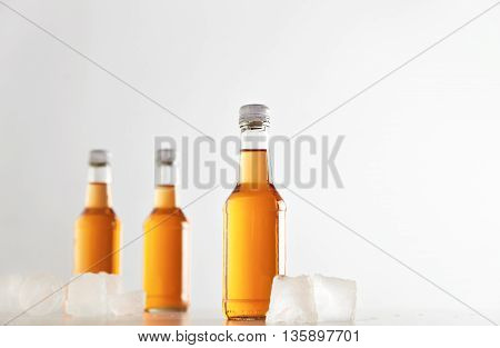 Three sealed bottles with cold cider drink inside isolated on white between ice cubes, presentation mockup