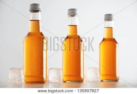 Unlabeled rustic bottles sealed with tasty cold drink inside presented next big ice cubes, isolated on white, retail mockup presentation