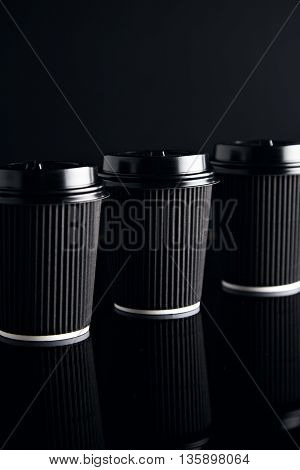 Closeup luxury set of black take away cardboard paper cups closed with caps isolated on black and mirrored. Retail mockup presentation