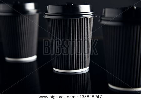 Black craft paper cups closed with caps isolated on black and mirrored. Retail mockup presentation
