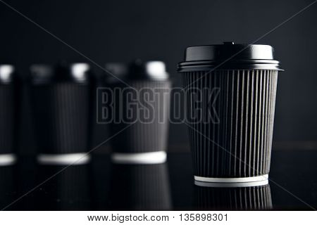 Luxury set of coffee take away cardboard paper cups closed with caps isolated on black and mirrored. Retail mockup presentation