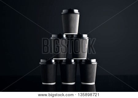 Blank set of black take away cardboard paper cups closed with caps in pyramid shape presented on black and mirrored. Retail mockup presentation