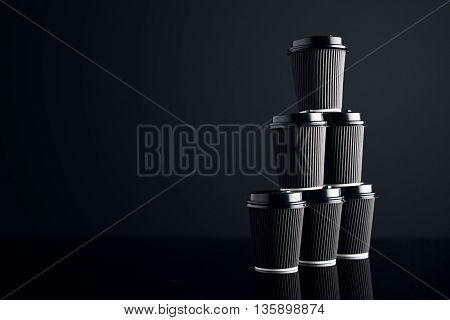 Blank set of black take away cardboard paper cups closed with caps in pyramid shape presented on right side, black and mirrored. Retail mockup presentation