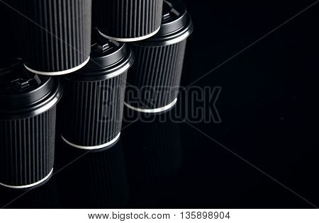 Closeup view on unlabeled set of black take away cardboard paper cups closed with caps in pyramid shape presented on side, black and mirrored. Retail mockup presentation