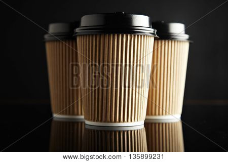 Three take away cardboard paper cups closed with caps isolated on black and mirrored. Retail mockup presentation