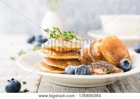 Dutch mini pancakes called poffertjes with blueberries and thyme, sprinkled with powdered sugar. Healthy food concept.