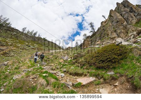 Hikers climbing uphill on steep rocky mountain trail. Summer adventures and exploration on the Alps. Dramatic sky with storm clouds.