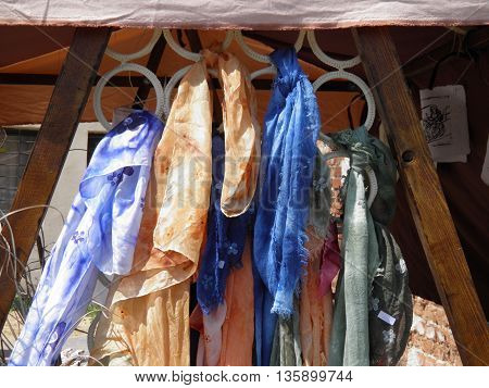 Light cotton foulards of different colours on hangers