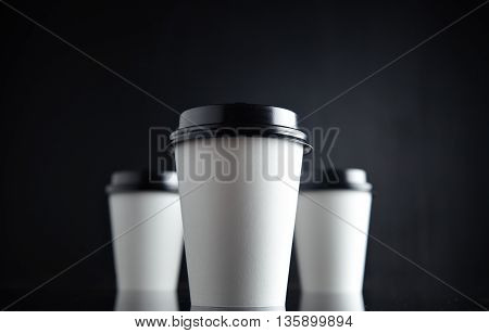 Bottom view to three take away white cardboard paper cups closed with black caps isolated in center and mirrored. Retail mockup presentation