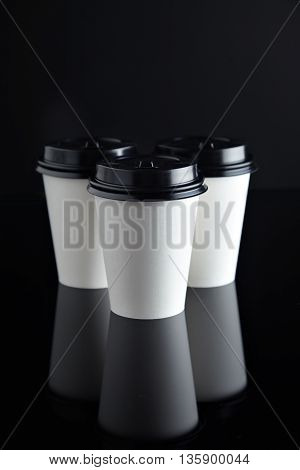 Set of three take away white coffee cardboard paper cups closed with black caps isolated in center and mirrored. Retail mockup presentation, top view