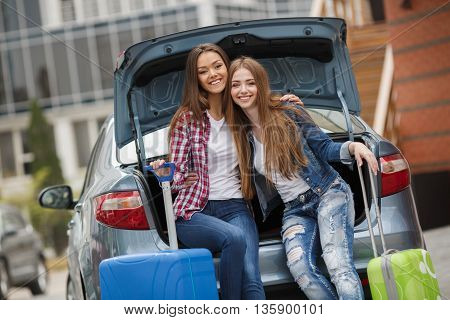 Happy girlfriends, two beautiful young brunette woman with long straight hair, nice smile, dressed in blue jeans, white t-shirt, posing sitting in the open trunk of the gray car, keep the blue and green suitcase on wheels