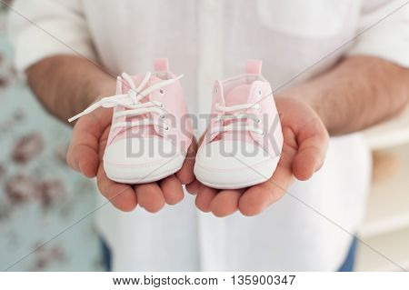 Hands Holding Baby Shoes. Waiting for the baby. Pregnancy. Hands of the man holding small shoes for a baby.