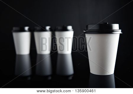 One focused white coffee take away paper cup ahead others unfocused, all closed with black caps presented on black and mirrored. Retail mockup presentation