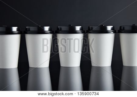 Many white take away paper cups for hot beverages closed with caps presented in line, isolated on black and mirrored. Retail mockup presentation