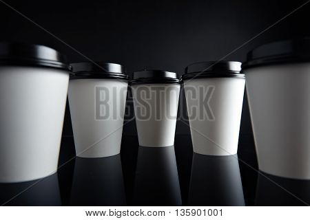 Many white take away paper cups for hot beverages closed with caps presented in parallax perspective, isolated on black and mirrored. Retail mockup presentation