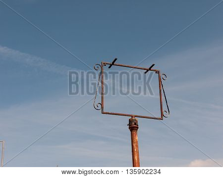 An empty rusted signpost in front of a clear blue sky.
