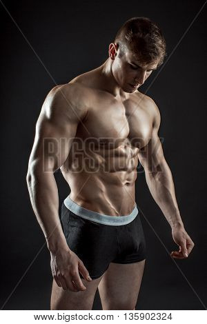 Muscular bodybuilder guy doing posing over black background. Naked torso in shorts.