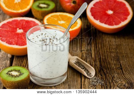 Chia pudding with orange grapefruit kiwi in the glass on the wooden table diet and health breakfast blank space for text