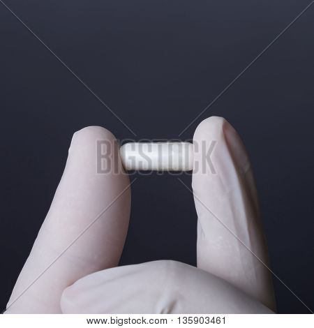 Hand in white latex glove holding white capsule. Doctor or nurse showing medicine. Dark background