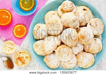 Sweet profiterole with cream powdered sugar fruit infused water for dessert top view