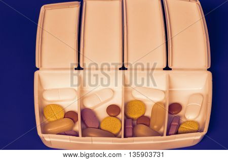 Dispenser with medicine pills on a blue background. Toned photo