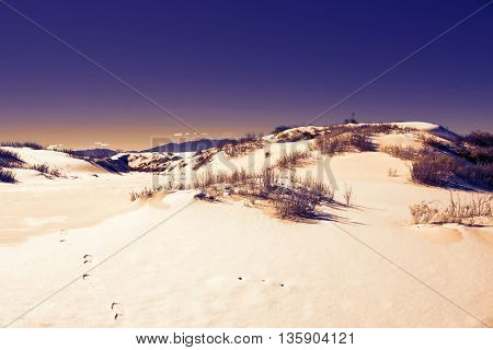 White gypsum sand of the desert with snow.  Toned image
