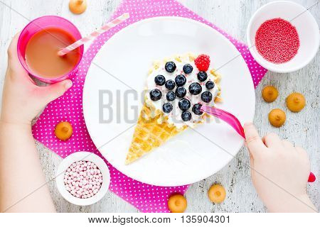 Creative baby breakfast idea - wafer with mascarpone cream and berries in shape ice cream. Child eating