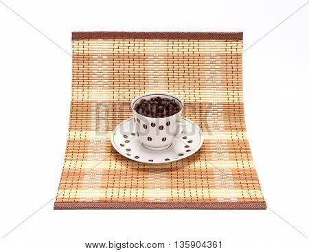 Coffee cup with coffee grains on a napkin on a white background