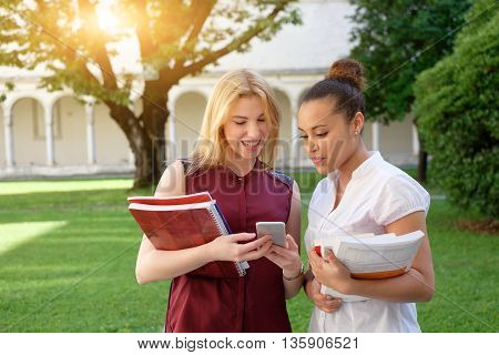 Two young females friends all together looking at mobile phone