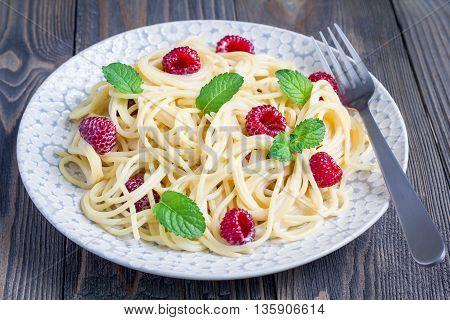 Spaghetti with sour cream honey and raspberries vegetarian on gray plate horizontal