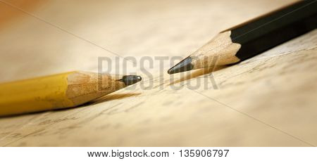Website banner of two old pencils on a letter