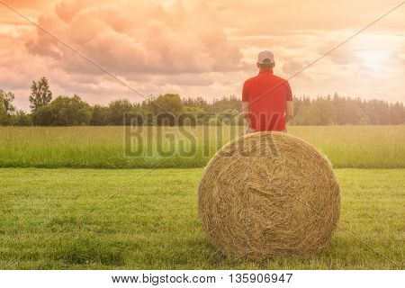 Man sitting back on a haystack in the field on a background cloudy sky
