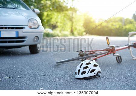 Broken bicycle on the asphalt after car crash incident