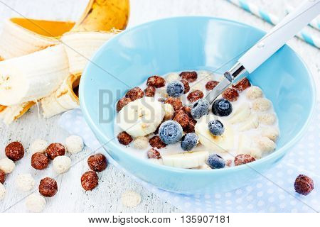 Healthy breakfast - cereal chocolate balls with milk berries and fruit selective focus