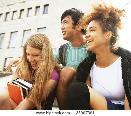 cute group of teenages at the building of university with books huggings
