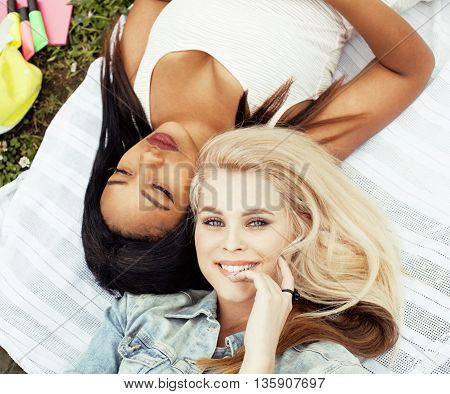 two pretty girls on grass happy smiling, best friends having fun together, lifestyle people concept close up