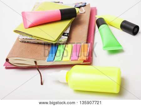 business, education and technology concept - close up of notebook, paper stickers, pencil and different stuff on white background, little mess