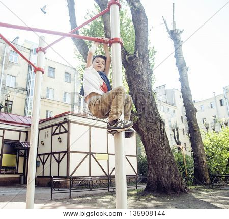 little cute blond boy hanging on playground outside, alone training with fun, lifestyle happy children concept