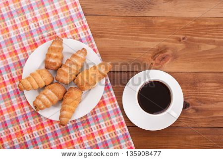 Coffee and sweet pastry rolls with filling on the wooden table.