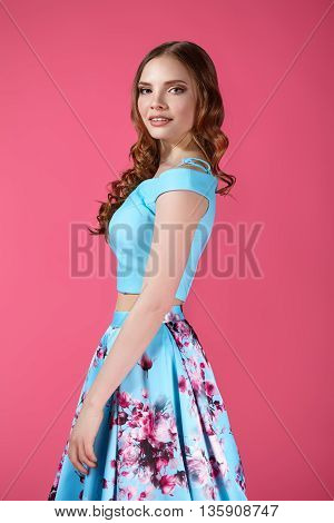 Fashion portrait of a young girl in a bright dress on a pink background.